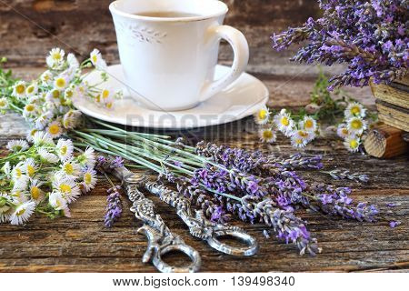 Аromatic lavender tea and wild chamomile on old wooden table