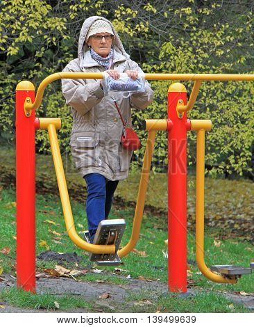 Old Woman Is Exercising In City Park Of Warsaw
