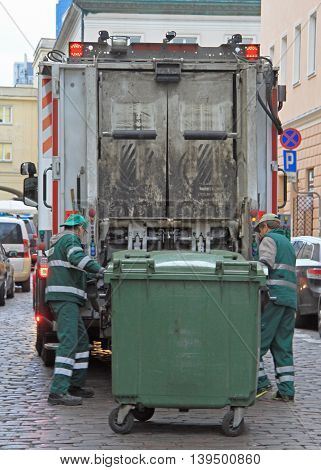 Warsaw, Poland - October 23, 2015:service workers is loading trash from dustbin to garbage truck outdoot in Warsaw, Poland