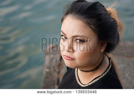 grumpy young asian woman looking at camera