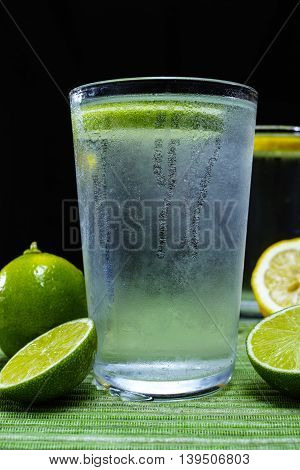 Glass with cold sparkling mineral water with fresh green lime seltzer