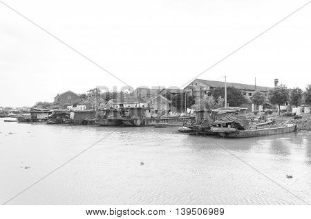A black and white picture of houseboats on the water near Xinshi Town located in Zhejiang Province China.