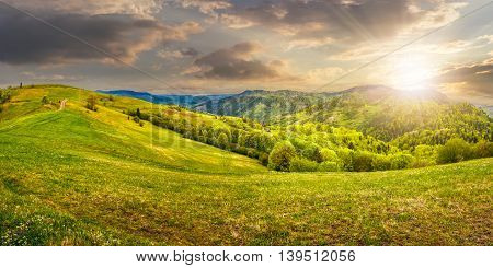 Idyllic view of pretty farmland rolling hills. Rural landscape near the forest in mountains in evening light