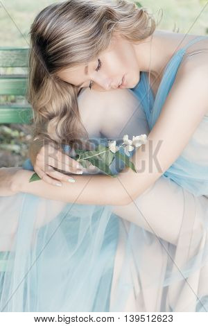 beautiful sexy tender blonde girl in a blue light dress with a sprig of jasmine in his hands sitting in the garden in the style of photos Fine Art