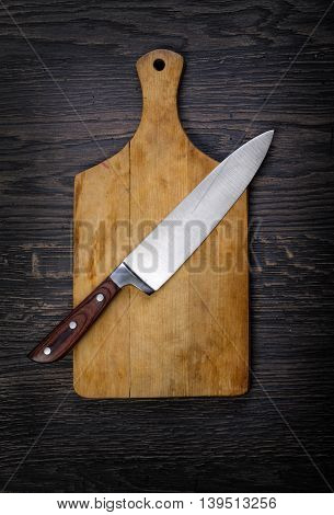 Empty chopping board with a knife on a distressed grunge wooden table