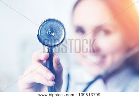 Smiling doctor holding phonendoscope blurred look. Concept of medical help.Film effect