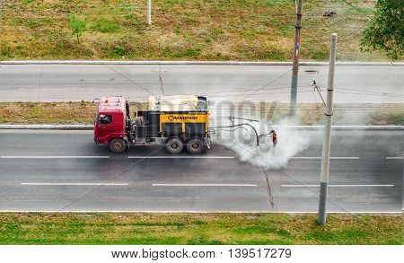 Orenburg Russia-July 07 2016: Worker is repairing road potholes with asphalt emulsion by Madpatcher machine