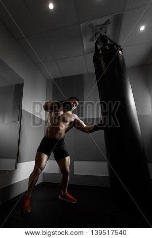 Male boxer training with punching bag in dark sports hall. Young boxer training on punching bag. Male boxer as exercise for the big fight. Boxer hits punching bag. Young masculine male athlete.