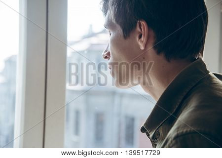 Young sad man looking out the window. close up.