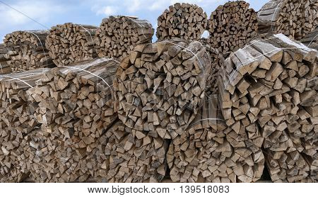 Stacked round bundles of wood with strappings outdoors
