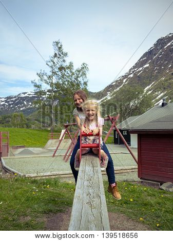 two happy girls on a swing at the playground norway