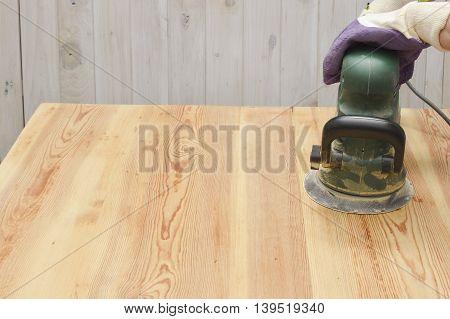 Electric Sander. Carpenter sanding a wood with sander