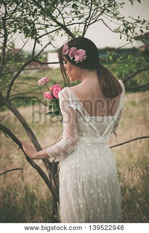 young woman in white lacy dress holding flowers stand by tree, back shot