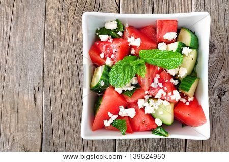 Summer Salad With Watermelon, Cucumber And Feta Cheese In A Square Bowl, Above View On Wood Backgrou