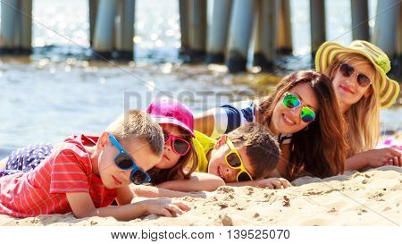 Happy family mothers daughter and sons sunbathing on beach sand. People parents and children kids at sea. Summer vacation holidays relax and happiness.