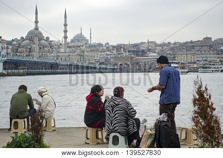 Istanbul Turkey - February 26 2013: Istanbul Golden Horn boats at sea. People who eat fish on the beach bread. Galata bridge and Eminonu looks new mosque in the background.