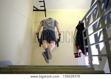Young man trains on two horizontal bars on wall indoor in entryway