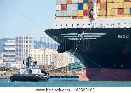 Oakland CA - July 18 2016: AmNav Tugboat PATRICIAN ANN off the bow of MSC KATRINA assisting the vessel to maneuver into the Port of Oakland. Tugboats are vital for safe efficient entry and exit for the large ships.