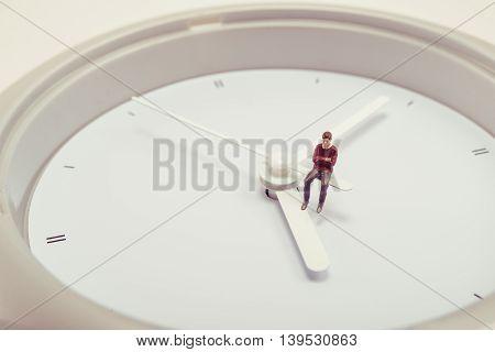 Miniature human doll sitting on the clock
