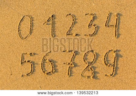 Numbers from 0 to 9 hand-drawn in the beach sand.