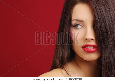 Close-up portrait of a beautiful brunette, red background