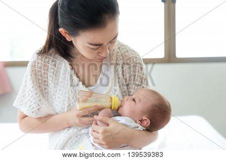 Feeding Baby infant. Asian mother feeding milk to her newborn baby infant with feeding bottle.