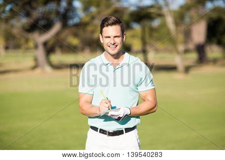Portrait of smiling golfer with score card while standing at golf course