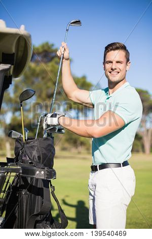 Portrait of smiling man putting golf club in bag while standing on field