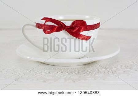 White tea cup with red bow on white background