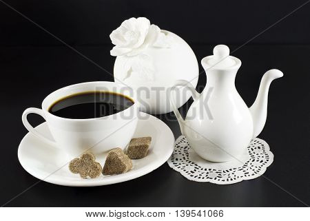 White set of dishes, cup of coffee and sugar on black