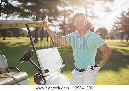 Portrait of smiling young man by golf buggy while standing on field
