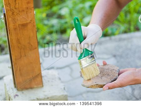 Man with protective glove sticking with putty knife broken stone to obtain refreshment of garden resting place.