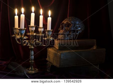 Mystic still life with candelabrum, skull and old book in the darkness