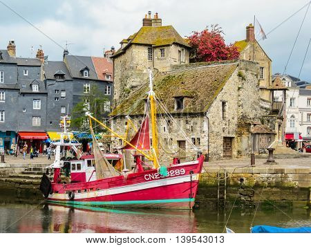 HONFLEUR FRANCE - MAY 6, 2014: Old boat and The Lieutenancy building or La Lieutenance is at the entrance to the old harbour. Honfleur, Normandy, France