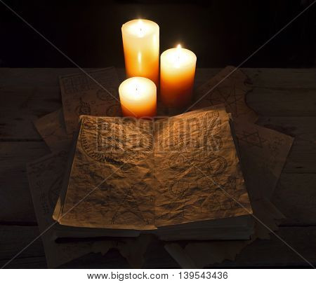 Open black magic book with three burning candles, Halloween concept