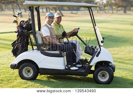 Portrait of happy male golfer friends sitting in golf buggy on sunny day