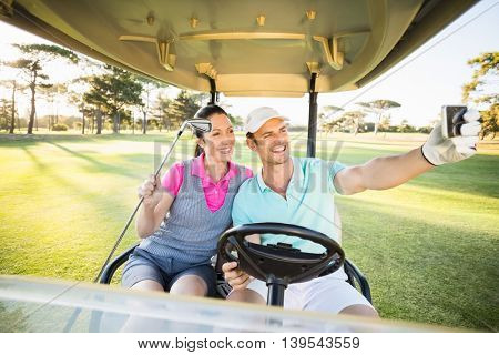 Smiling golfer couple taking self portrait while sitting in golf buggy on field