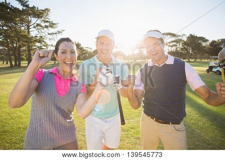 Portrait of cheerful golfer friends standing on field