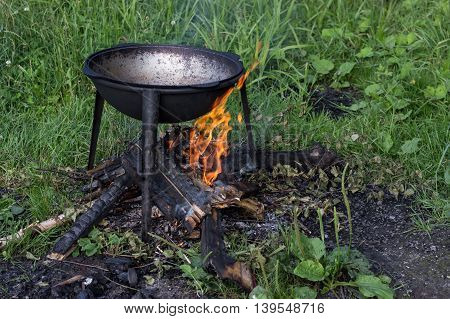 cauldron (kazan) on fire cooking outdoors in summer in forest