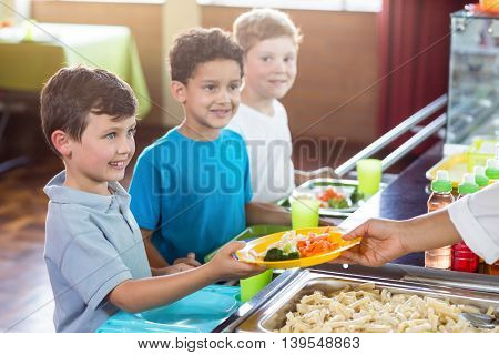 Cropped image of woman serving food to smiling schoolchildren in canteen