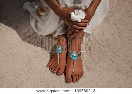 closeup photo of beautiful young bride legs with anklets. holding flower in her arms.
