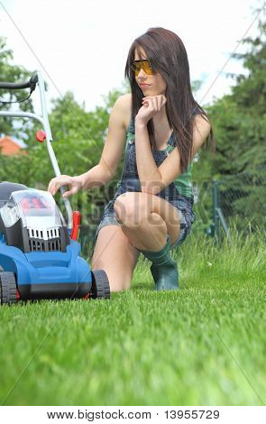 garden work, woman mowing grass with lawnmower
