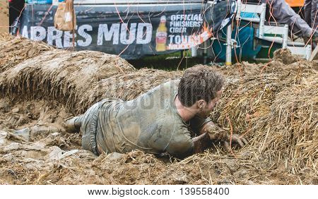 Grantham, Leicestershire/UK-May 21, 2016: A participant is shocked to the ground by the Electro Shock Therapy obstacle at the 2016 Tough Mudder extreme sports charity competition at Belvoir Castle.