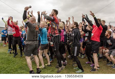 Grantham Leicestershire/UK - May 21, 2016: Excited participants jumping up and down during the warm-up ahead of the 2016 Tough Mudder extreme sports charity competition at Belvoir Castle.