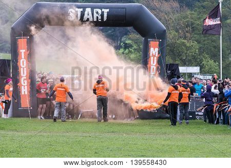 Grantham Leicestershire/UK - May 21, 2016: Tough Mudder volunteers pop the orange smoke as participants ready to take on the 2016 Tough Mudder extreme sports charity competition at Belvoir Castle.