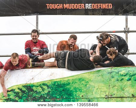 Grantham, Leicestershire/UK - May 21, 2016: Participants team up to pull another person up the Everest 2.0 obstacle at the 2016 Tough Mudder extreme sports charity competition at Belvoir Castle.