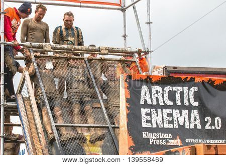 Grantham, Leicestershire/UK - May 21, 2016: Participants slide into the chilling waters of the Arctic Enema 2.0 obstacle at the 2016 Tough Mudder extreme sports charity competition at Belvoir Castle.