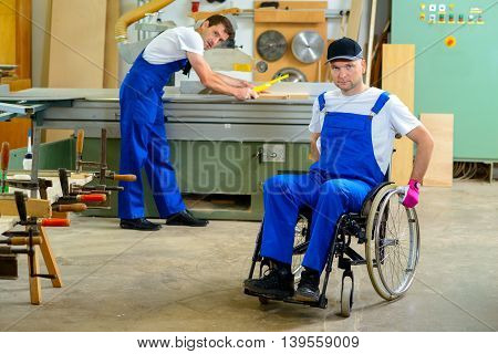Worker In Wheelchair In A Carpenter's Workshop With His Colleagu