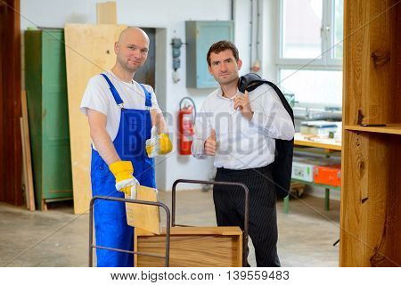 Boss And Worker With Thumb Up In A Carpenter's Workshop