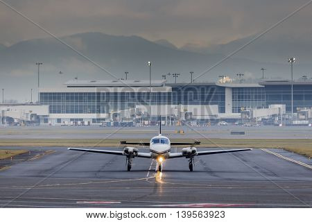 Small aircraft taxiing at airport in bad weather